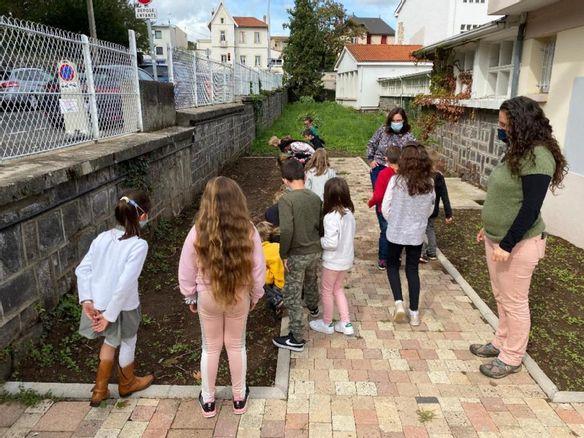 Petit groupe d'élèves devant un potager